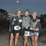 Runners at finish line on Race Day 1 and moon rise in the backdrop
